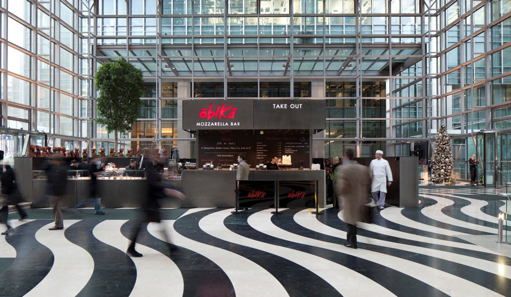 Obika Canary Wharf, London, United Kingdom. Architect: Labics, 2012. Exterior of restaurant with customers, and wavy black and white stripy flooring. : Stock Photo
