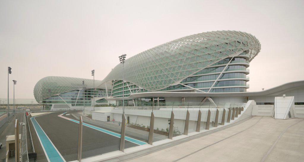 Stock Photo: 1801-74360 Yas Hotel, Abu Dhabi, United Arab Emirates. Architect: Asymptote, Hani Rashid, Lise Anne Couture, 2010. General view with race track.
