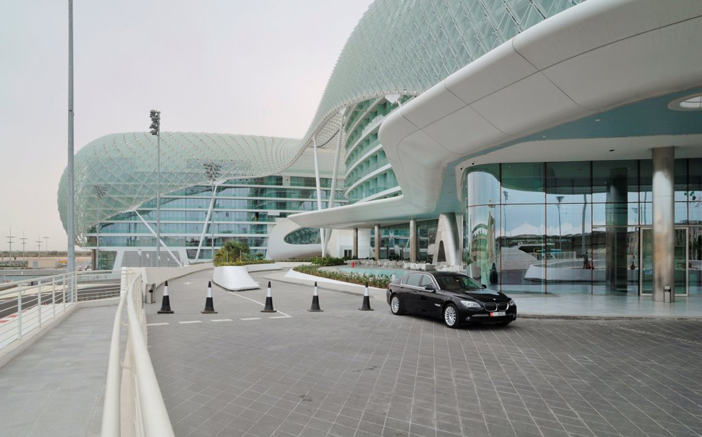 Stock Photo: 1801-74361 Yas Hotel, Abu Dhabi, United Arab Emirates. Architect: Asymptote, Hani Rashid, Lise Anne Couture, 2010. Entrance view with car.