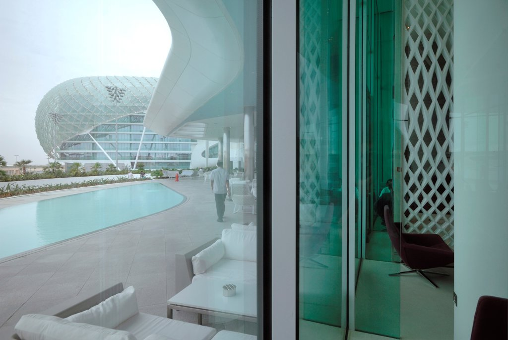 Stock Photo: 1801-74382 Yas Hotel, Abu Dhabi, United Arab Emirates. Architect: Asymptote, Hani Rashid, Lise Anne Couture, 2010. View of the pool through curtain wall.