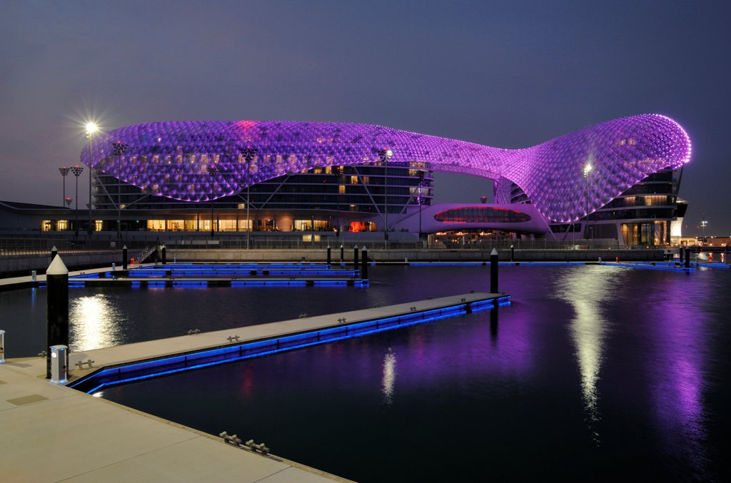 Stock Photo: 1801-74388 Yas Hotel, Abu Dhabi, United Arab Emirates. Architect: Asymptote, Hani Rashid, Lise Anne Couture, 2010. General view from Marina with purple LED skin.