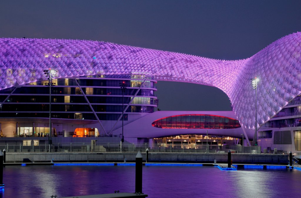Yas Hotel, Abu Dhabi, United Arab Emirates. Architect: Asymptote, Hani Rashid, Lise Anne Couture, 2010. General view from Marina with purple LED skin. : Stock Photo
