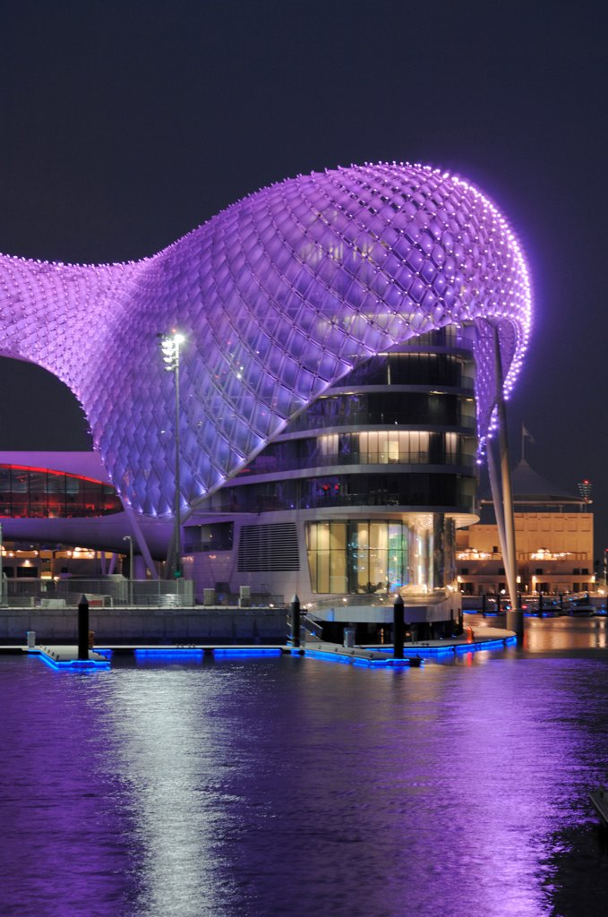 Stock Photo: 1801-74393 Yas Hotel, Abu Dhabi, United Arab Emirates. Architect: Asymptote, Hani Rashid, Lise Anne Couture, 2010. General view from Marina with purple LED skin.