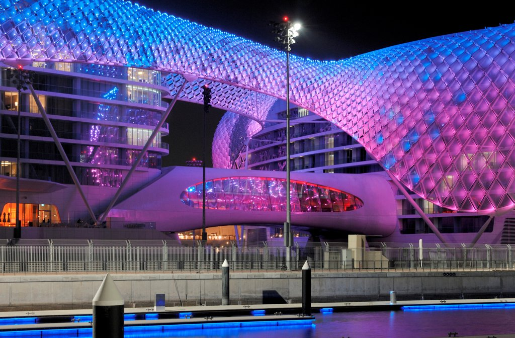 Yas Hotel, Abu Dhabi, United Arab Emirates. Architect: Asymptote, Hani Rashid, Lise Anne Couture, 2010. General view from Marina with blue and purple LED skin. : Stock Photo