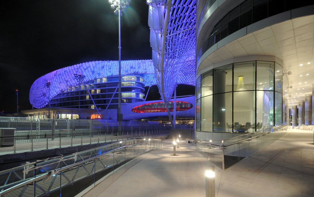 Stock Photo: 1801-74400 Yas Hotel, Abu Dhabi, United Arab Emirates. Architect: Asymptote, Hani Rashid, Lise Anne Couture, 2010. Night view of outside deck.