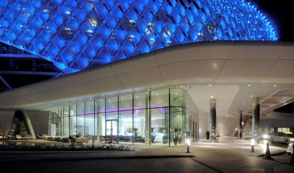 Yas Hotel, Abu Dhabi, United Arab Emirates. Architect: Asymptote, Hani Rashid, Lise Anne Couture, 2010. Side view by night with car way. : Stock Photo