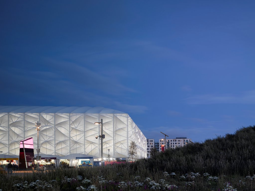 Stock Photo: 1801-74516 Basketball Arena, London 2012 Olympics, London, United Kingdom. Architect: Wilkinson Eyre Architects, 2012. Dusk shot with flowers.