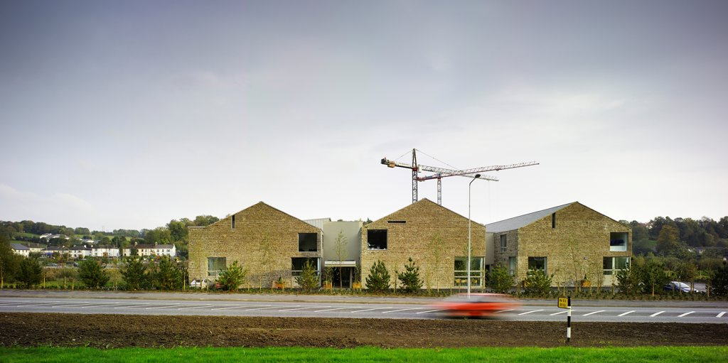 Stock Photo: 1801-74666 Cavan College, Cavan, Ireland. Architect: McCullough Mulvin , 2006. View of West facade showing road, surrounding landscape and the stone gables of the three blocks.