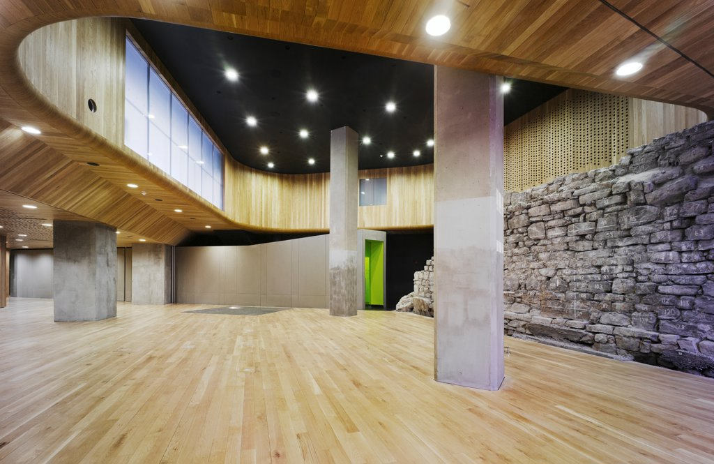 Dublin City Walls, Dublin, Ireland. Architect: McCullough Mulvin, 2009. View of conference space showing Viking City Walls, concrete corridor with painted green interior, concrete supports and timber ceiling surrounding a double height space. : Stock Photo