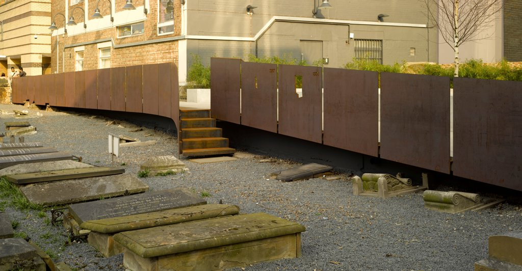 Novo Cemetery, Queen Mary University, London, United Kingdom. Architect: Seth Stein, 2012. Overall view from cemetery showing corten steel raised walkway. : Stock Photo