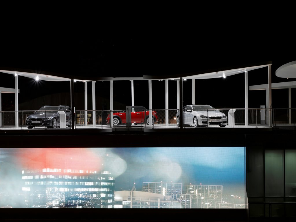 BMW Group Pavilion London 2012, London, United Kingdom. Architect: Serie Architects, 2012. Night shot of structure with cars and graphics. : Stock Photo
