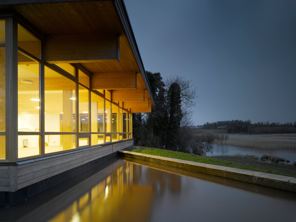 Stock Photo: 1801-75328 Ballybay Wetland Centre, Ballybay, Ireland. Architect: Solearth Ecological Architecture, 2008. View of building showing surrounding landscape and interior lighting at dusk.