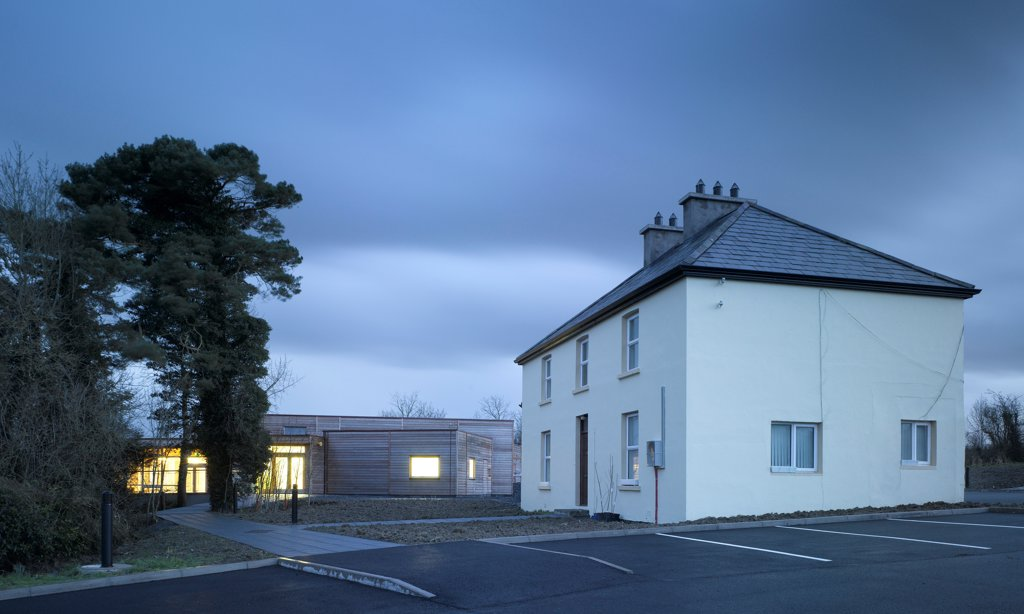 Stock Photo: 1801-75329 Ballybay Wetland Centre, Ballybay, Ireland. Architect: Solearth Ecological Architecture, 2008. View of building from car park showing existing structure, timber cladding and interior lighting at dusk.