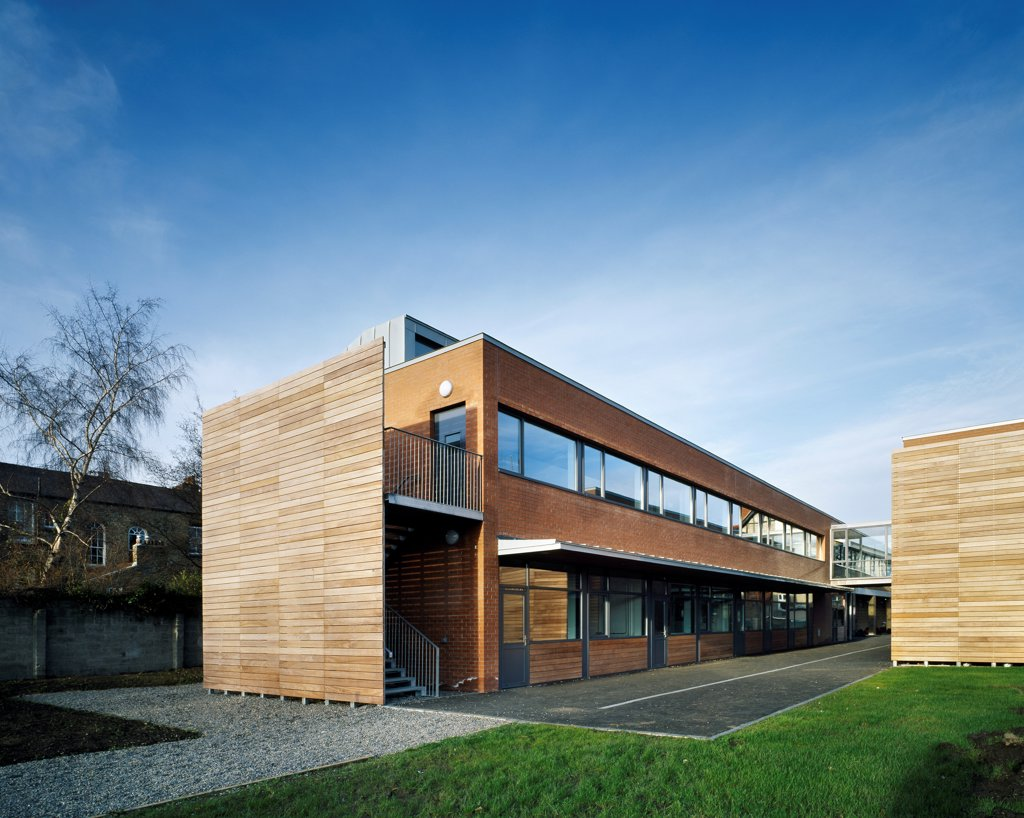 Stock Photo: 1801-75359 Sandford Park School, Ranelagh, Ireland. Architect: DTA Architects, 2007. View of classrooms showing timber and brick cladding and path through school ground.