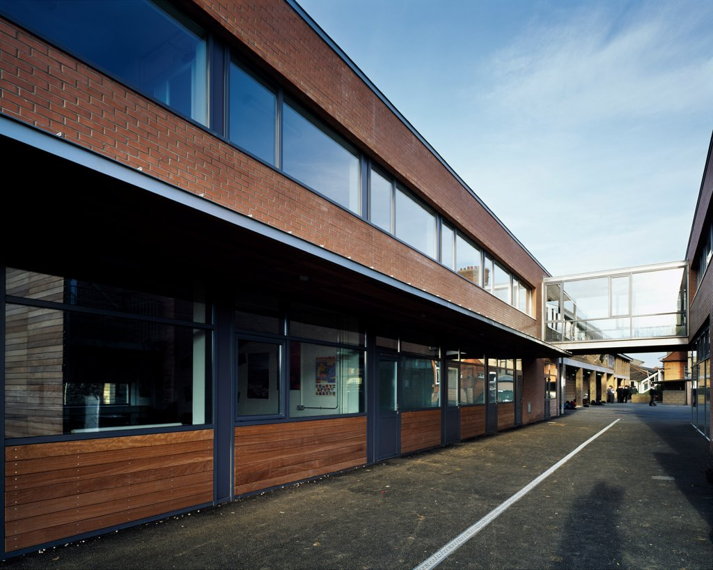 Stock Photo: 1801-75360 Sandford Park School, Ranelagh, Ireland. Architect: DTA Architects, 2007. View of path through school grounds showing classrooms with timber and brick cladding.