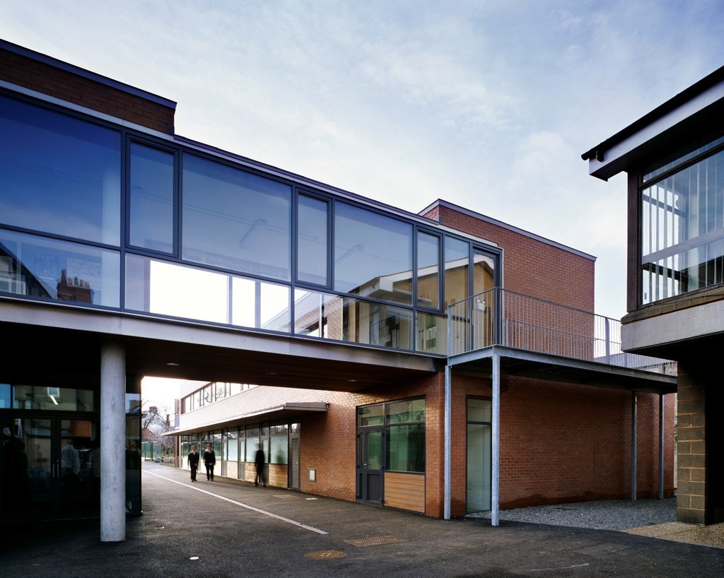 Sandford Park School, Ranelagh, Ireland. Architect: DTA Architects, 2007. View of bridge between classrooms showing concrete supports, brick cladding and path through school grounds. : Stock Photo