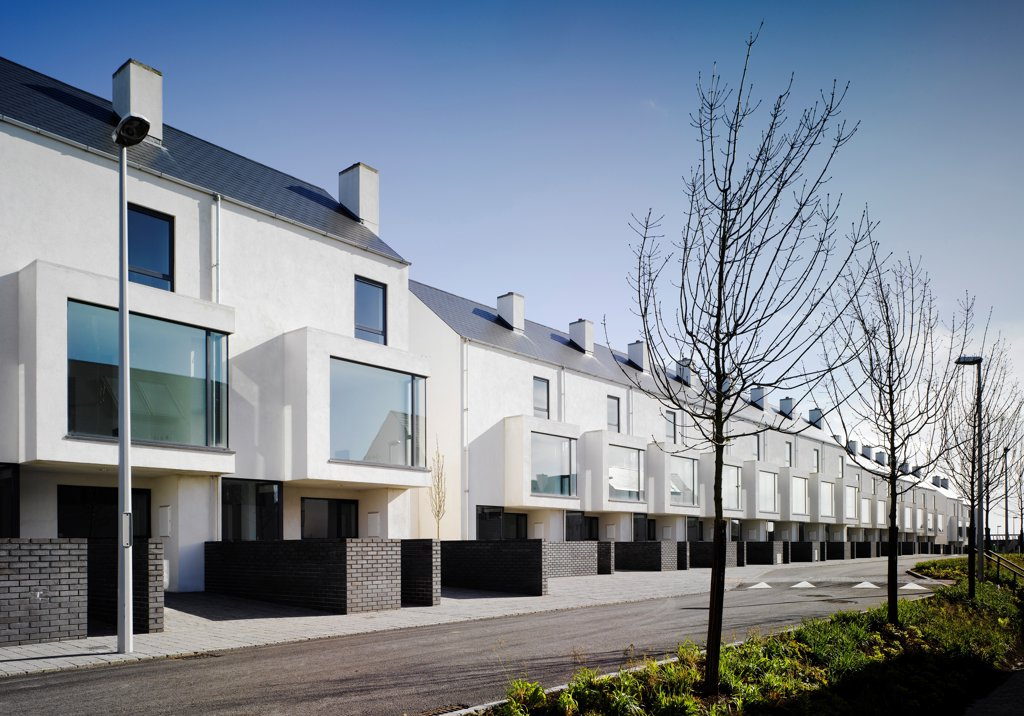 Stock Photo: 1801-75370 Gleann Bhan, Galway, Ireland. Architect: DTA Architects, 2008. View of terraces from road showing brick wall and trees.