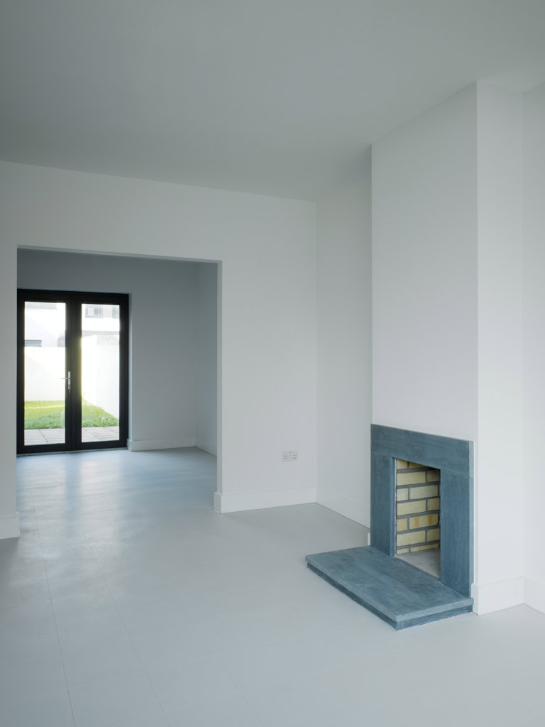 Stock Photo: 1801-75381 Gleann Bhan, Galway, Ireland. Architect: DTA Architects, 2008. View of living space showing fireplace and view to exterior.