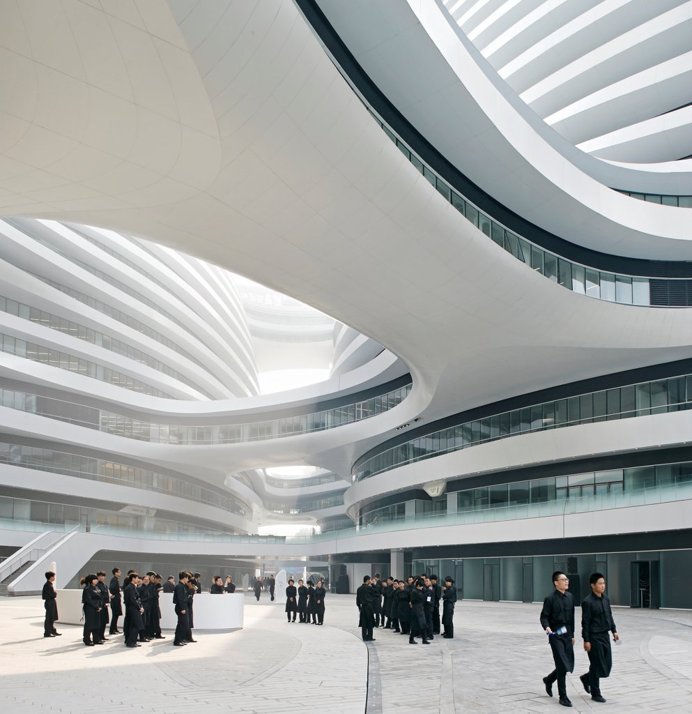 Galaxy Soho, Beijing, China. Architect: Zaha Hadid Architects, 2012. View into interior courtyard with organised staff. : Stock Photo