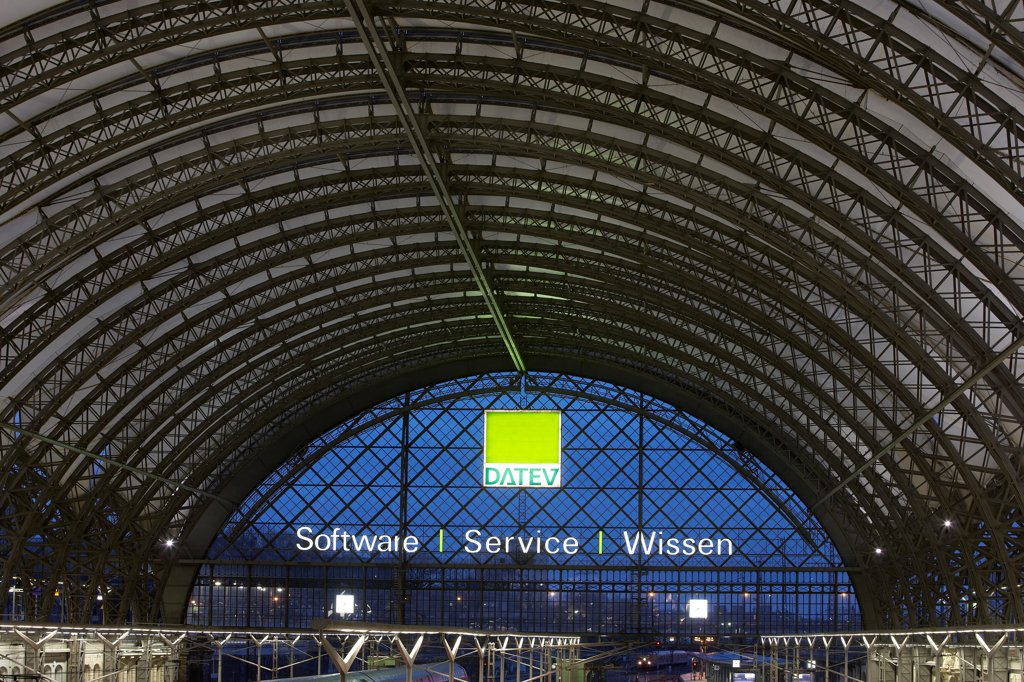 Stock Photo: 1801-76278 Dresden Hauptbahnhof, Dresden, Germany. Architect: Foster + Partners, 2006. General view of steelwork roof structure with translucent glass fibre skin and neon light advertising.