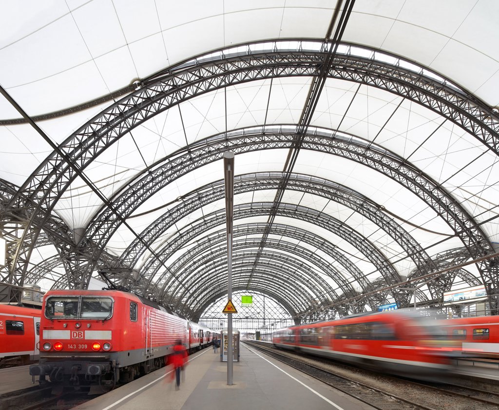 Stock Photo: 1801-76281 Dresden Hauptbahnhof, Dresden, Germany. Architect: Foster + Partners, 2006. View of platform with barrel-vaultet roof and trains in motion.