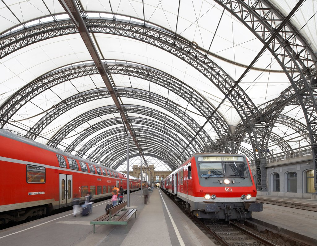 Stock Photo: 1801-76282 Dresden Hauptbahnhof, Dresden, Germany. Architect: Foster + Partners, 2006. View of platform with barrel-vaultet roof and trains.