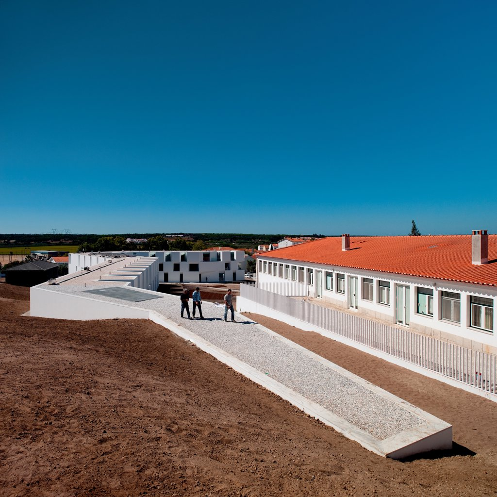 Stock Photo: 1801-77023 House for Elderly People, Alcaçer do Sal, Portugal. Architect: Francisco Aires Mateus Arquitectos, 2011. Context view of social housing complex in daylight with people.
