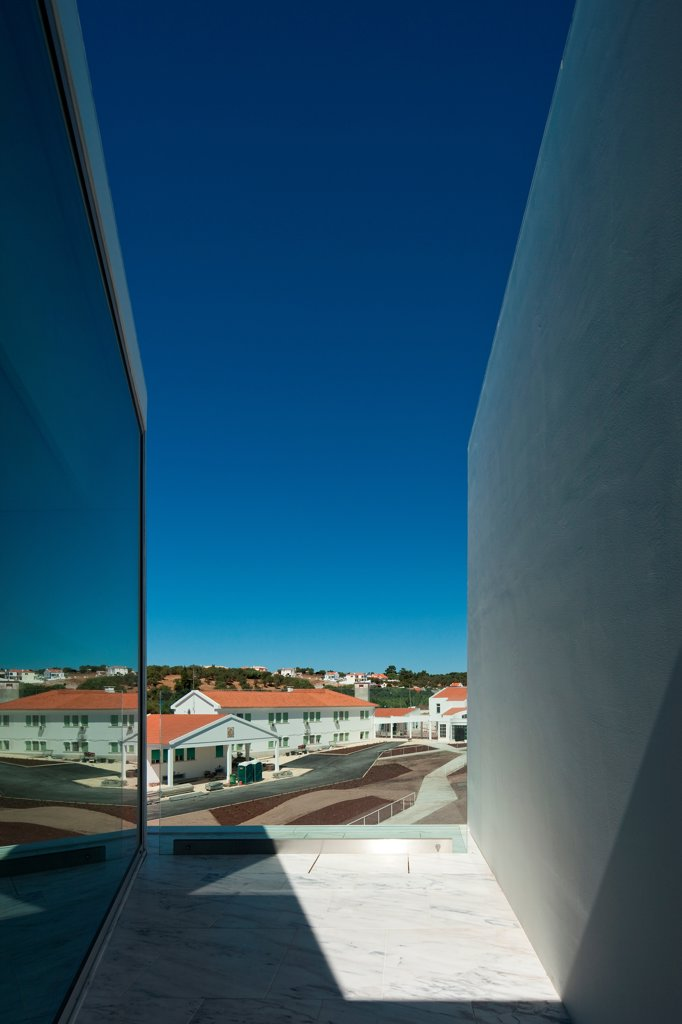 Stock Photo: 1801-77050 House for Elderly People, Alcaçer do Sal, Portugal. Architect: Francisco Aires Mateus Arquitectos, 2011. View from social housing complex in daylight to town.