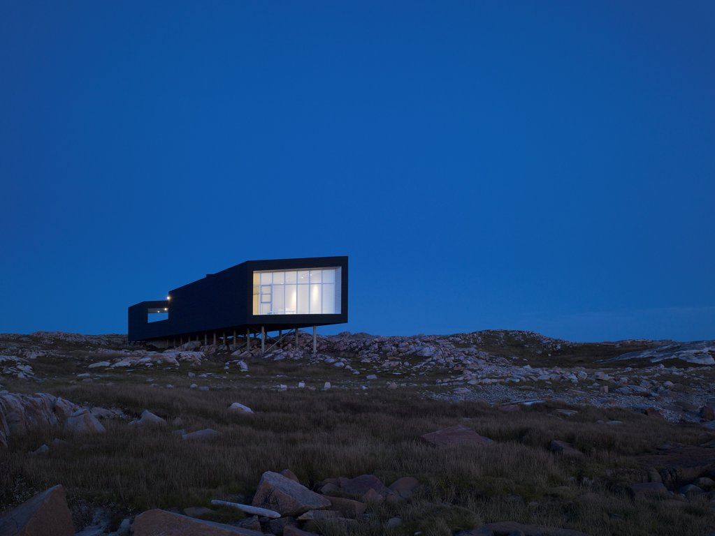 Stock Photo: 1801-77327 Long Studio, Fogo Island, Canada. Architect: Todd Saunders, 2011. Night-time view from beach.