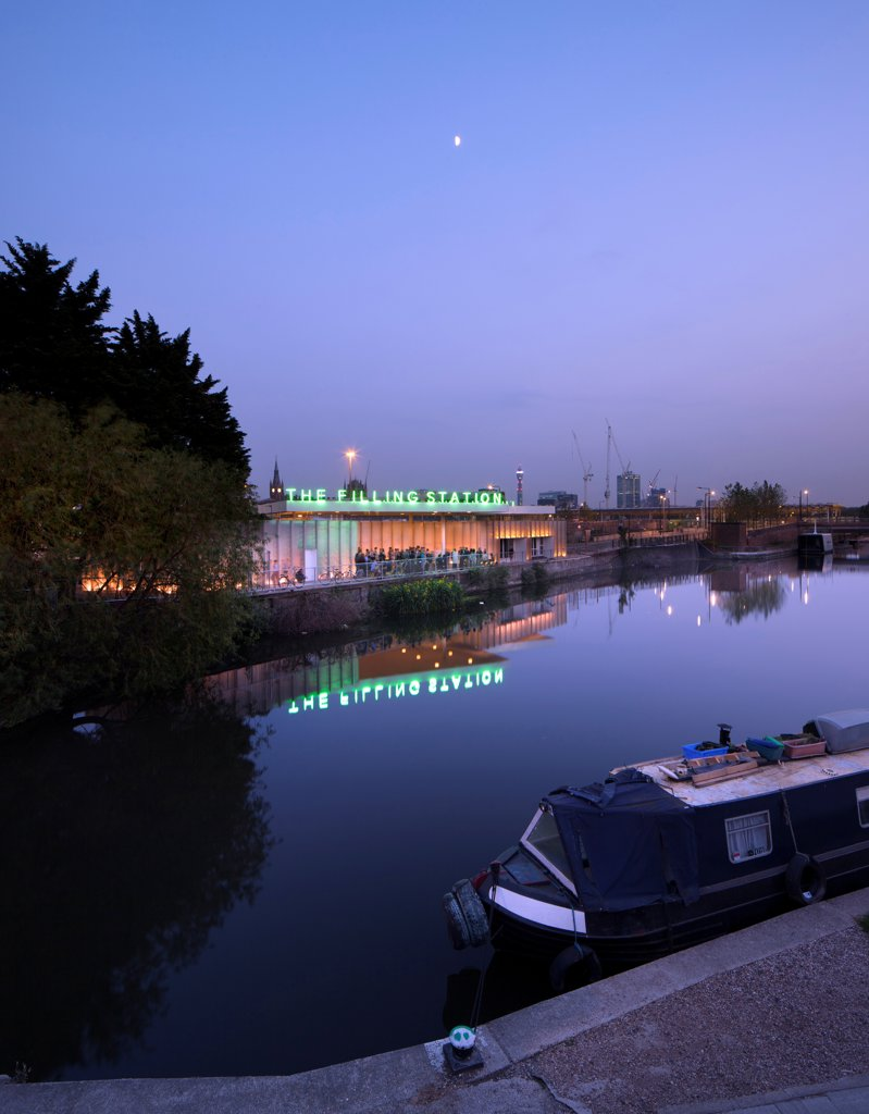 The Filling Station, London, United Kingdom. Architect: Carmody Groarke, 2012. Night time exterior looking across the Regents Canal, with a barge in the foreground. : Stock Photo