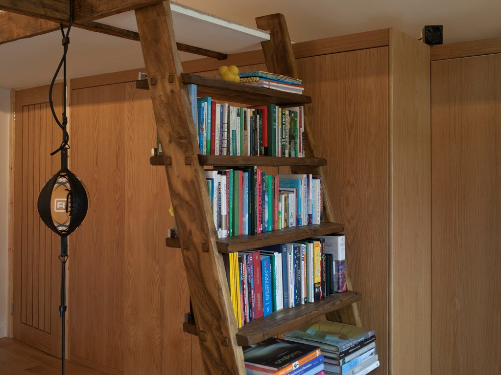 Stock Photo: 1801-78259 Garden Office, Berkhamsted, United Kingdom. Architect: SDP Design, 2012. Interior room detail showing bookcase, ladder and punch ball.  Timber wall panelling to background.