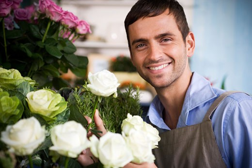 Male florist amongst the flowers in his shop : Stock Photo