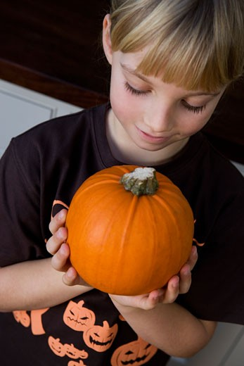 Little girl holding an orange Hallowe'en pumpkin : Stock Photo