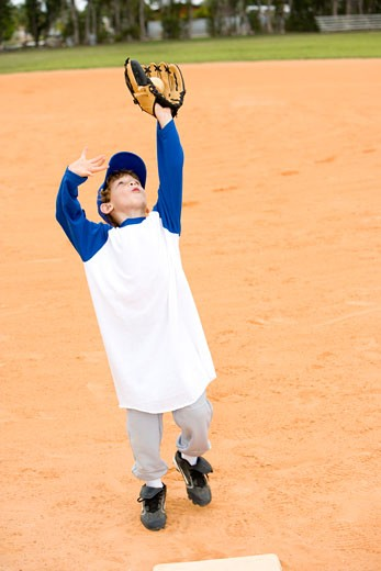 Young boy taking catch in baseball : Stock Photo