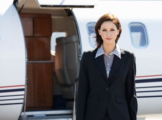 Stock Photo: 1804R-1049 A business woman standing by a plane