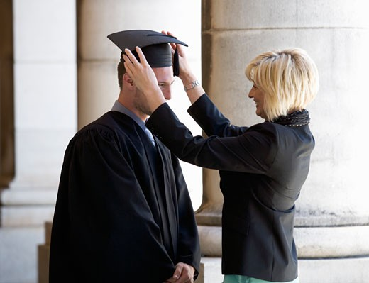 Stock Photo: 1804R-10582 A mother checking her graduate son's gown