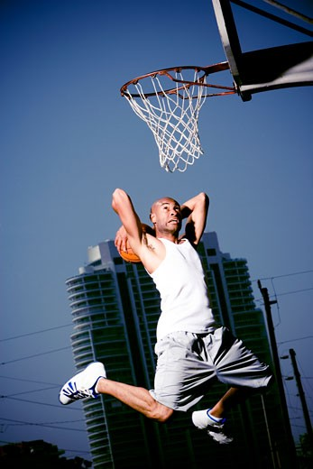 Young  African American man jumping with a basketball on an urban basketball court : Stock Photo