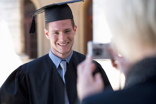 A graduate posing for a family photograph : Stock Photo