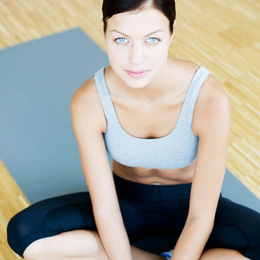A young woman sitting on a yoga mat : Stock Photo