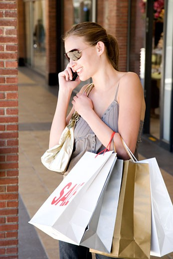 Stock Photo: 1804R-11339 Young woman with shopping bags talking on mobile phone
