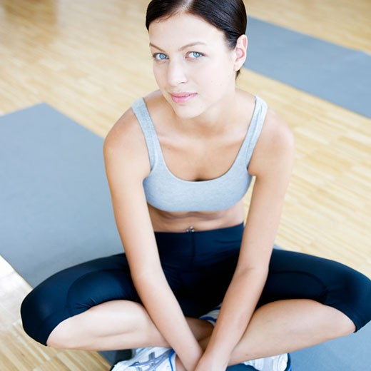 Stock Photo: 1804R-11479 A young woman sitting on a yoga mat