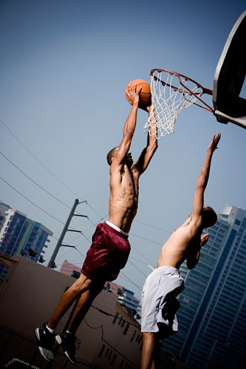 Two Young African American man jumping with a basketball on an urban basketball court : Stock Photo