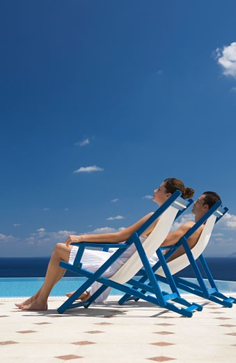 A couple relaxing in deck chairs : Stock Photo
