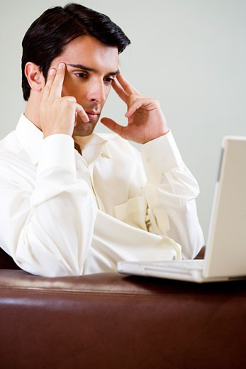 Portrait of a man with a headache, fingers on temples using a laptop computer : Stock Photo
