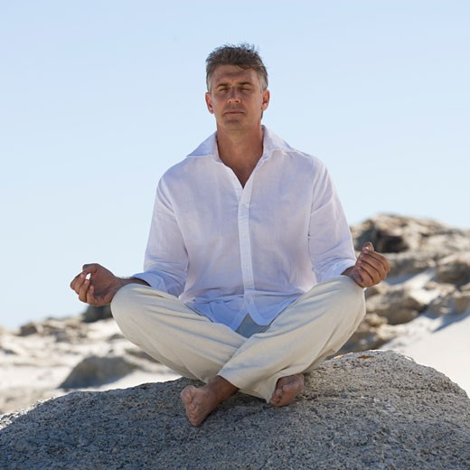 Stock Photo: 1804R-11911 A man sitting on rocks performing yoga