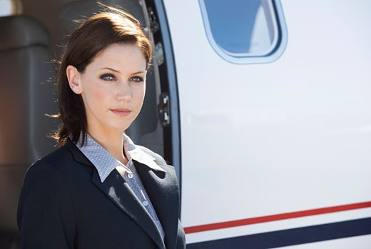 A business woman standing by a plane : Stock Photo