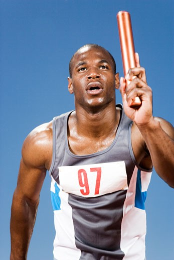 Relay runner with baton in his hand : Stock Photo