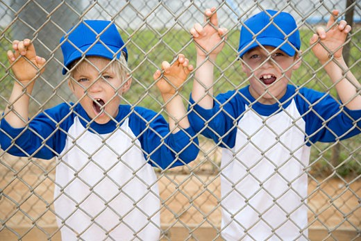 two boys roaring like lions through fence at baseball pitch : Stock Photo