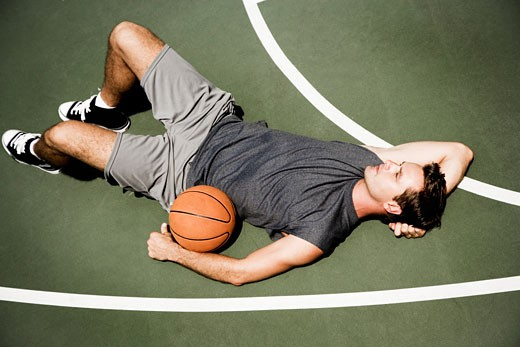 Stock Photo: 1804R-12429 Man laying down on an outdoor basketball court