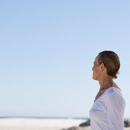 A mature woman standing on a beach : Stock Photo